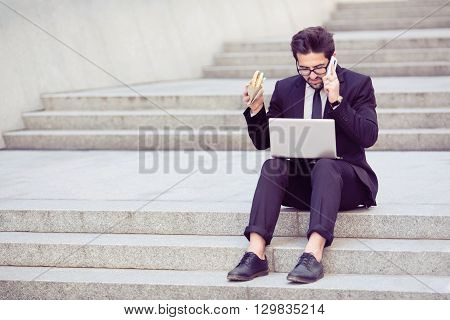 Toned picture of young businessman speaking over mobile or smart phone and looking at laptop computer's screen. Freelance man working in city centre and eating hamburger.