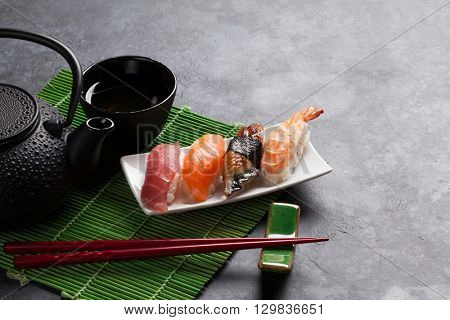 Set of sushi and green tea on stone table. View with copy space