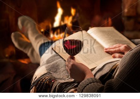 Woman resting with glass of red wine and book near fireplace