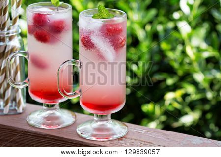 Pink refreshing cold raspberry lemonade in tall glasses outside on the porch