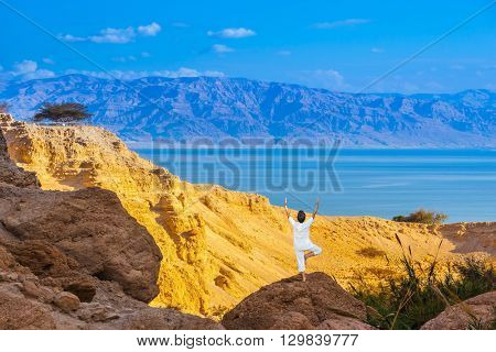 Elderly woman practices yoga on a rock near the Dead Sea. Travel national parks and reserves Ein Gedi, Israel