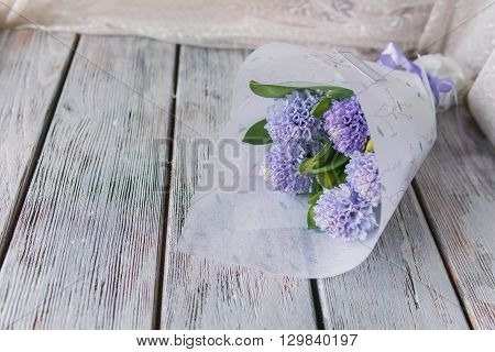 Background with fresh pink, violet and blue  hyacinths on    wooden planks. Selective focus. Place for text. Square image.