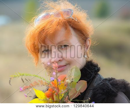 portrait of a pretty woman with a bouquet of flowers outdoors age 50 years
