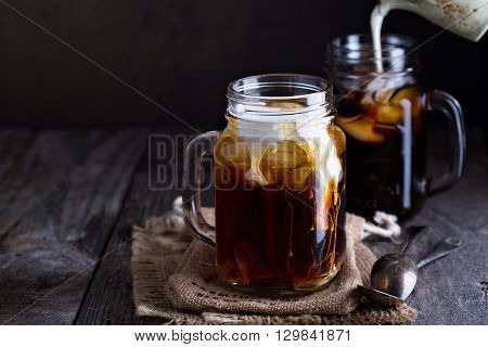 Iced coffee with milk in mason jars  on the table