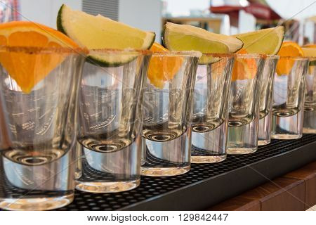 Little Transparent Glasses in Line with Orange and Lime Slices Ready to Tequila Shots