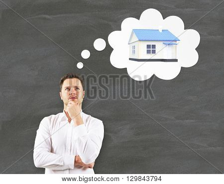 Mortgage concept with businessman thinking about house on chalkboard background