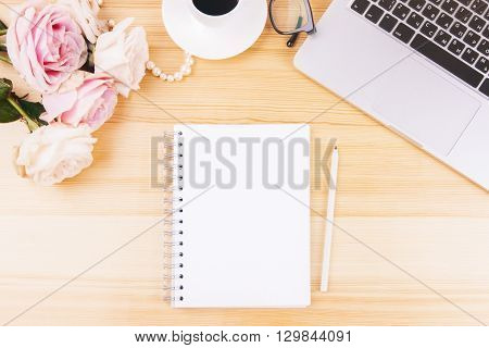 Top view of woman's desktop with blank spiral notepad flowers laptop keyboard and other items. Mock up