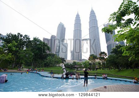 KUALA LUMPUR MALAYSIA - MAY 8 2016: Children at the pool in Kuala Lumpur urban area KL Central Park with buildings in the background having fun outdoors