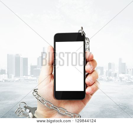 Smartphone with blank white screen cuffed to male hand on foggy city background. Concept of social problem. Mock up 3D Rendering