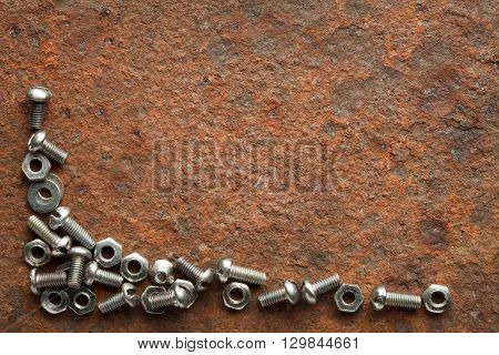 Bolts and nuts on rusted iron plate with copy space for text