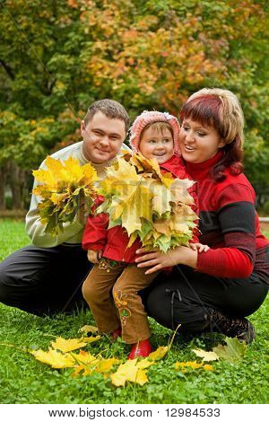Married couple and little girl collect maple leafs In park in autumn