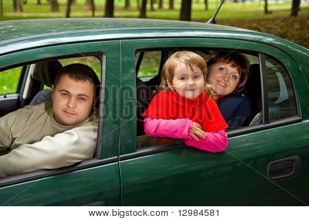 Married couple and  little girl sit in car in park