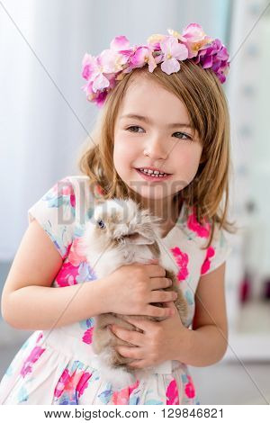 Beautiful little girl four years old holding white rabbit