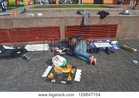 Dirty poor homeless man sleeps on Khreshatik - central street of Kiev.At April 8,2016 in Kiev, Ukraine