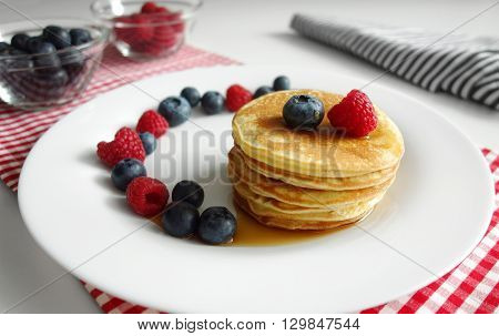 Blueberry pancake day breakfast background with a stack of delicious pancakes with fresh blueberries raspberries and maple syrup.