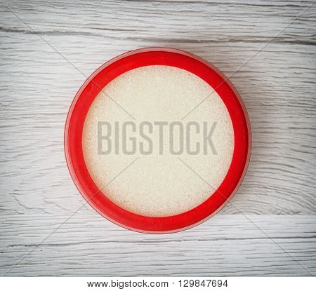Round plastic sponge case for dipping fingers. Office supplies.