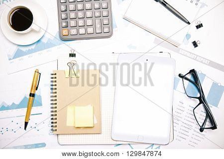 Topview of desk with white tablet notepad calculator and other office tools. Mock up