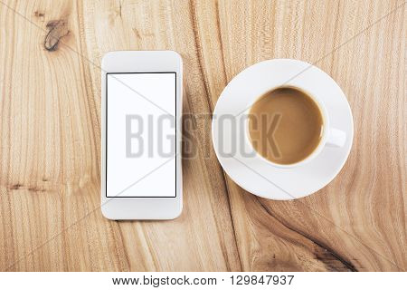 Topview of blank cellphone and coffee cup with saucer on natural wooden table. Mock up