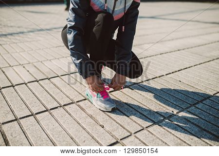 Female Jogger Tying Her Running Shoes Preparing For A Jog