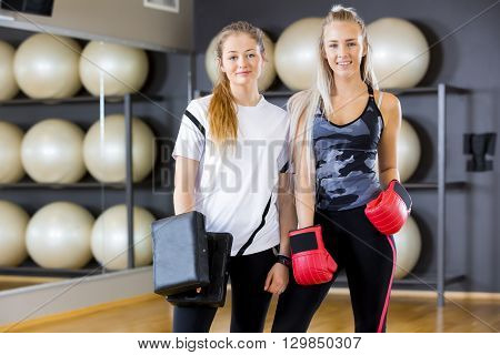 Environmental portrait of two young women takes a break from boxing training. Sparring in pairs as workout at the fitness gym.