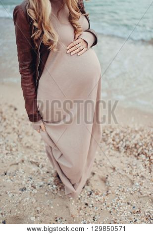 against the background of the beach by the sea belly of a pregnant woman in a long dress and jacket