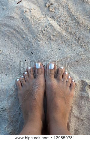 Two female bare feet on white sand.