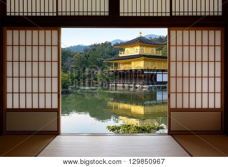 View of a beautiful Japanese golden temple and pond garden seen through open rice paper doors