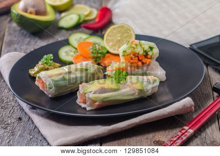 Spring rolls with vegetables and avocado on plate served with soy sauce