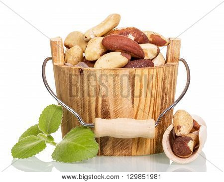 Roasted peanuts in a wooden bucket and a sprig of mint isolated on white background.