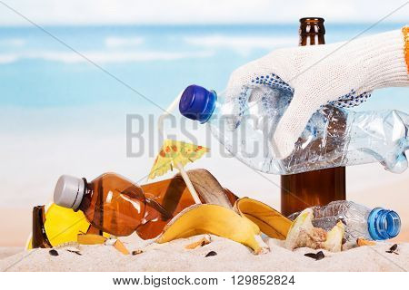 Hand holding a plastic bottle on a pile of garbage in the sand background.