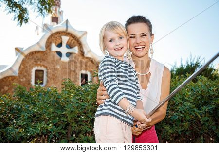 Smiling Mother And Daughter Taking Selfie In Park Guell