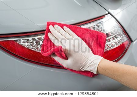 Car detailing series : Closeup of hand cleaning gray car