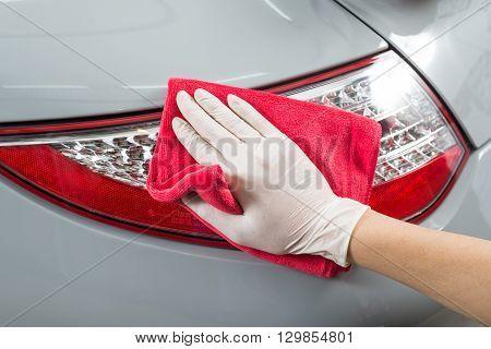 Car detailing series : Closeup of hand cleaning gray car