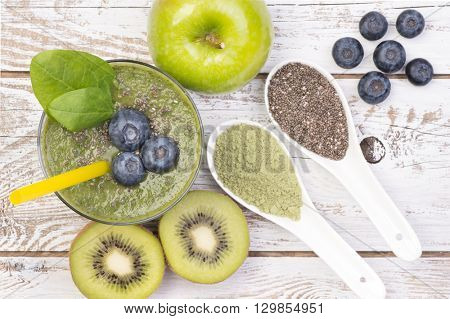 Green smoothie with young barley, chia seeds and blueberries on white, wooden background, top view