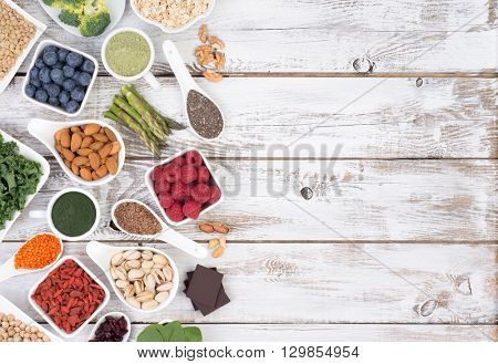 Healthy food called super foods on white, wooden background with copy space, top view