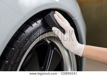 Car detailing series : Closeup of hand coating car tire