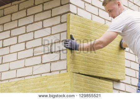 construction worker insulating house facade with mineral rock wool