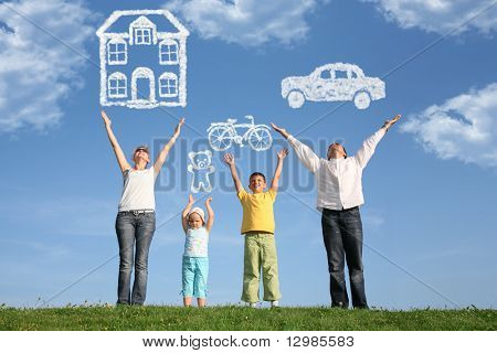 family of four on grass with hands up and dream