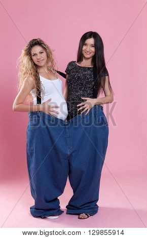 Portrait of a young pregnant women wearing a very large jeans Conceptual image about weight loss themes.
