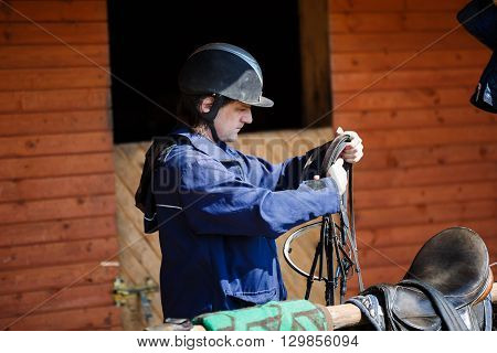 Rider holding a horse harness before training in the stables