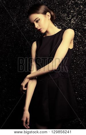 Vogue shot of a brunette young woman with magnificent brown eyes posing over black background. Studio shot.