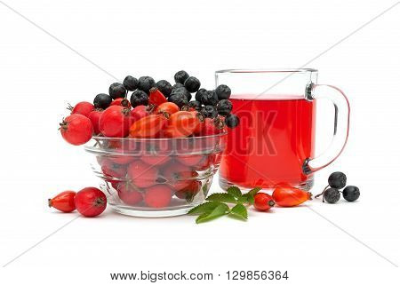 cup of tea with rose hips and different ripe berries on a white background. horizontal photo.
