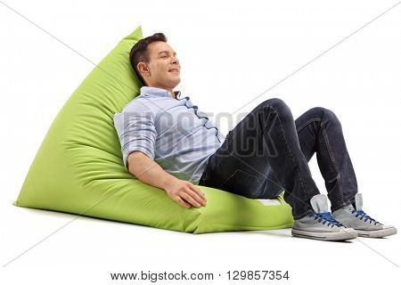 Relaxed young guy sitting on a soft and comfortable green beanbag isolated on white background