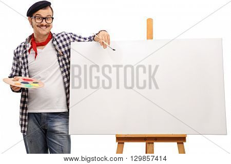 Eccentric artist posing next to a blank canvas on a wooden easel isolated on white background