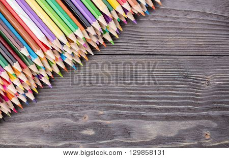 Set of color pencils on dark gray wooden background