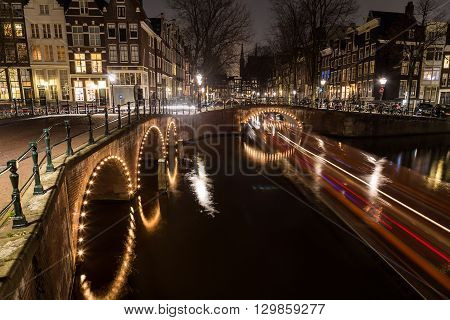 A view of the bridges at the Leidsegracht and Keizersgracht canals intersection in Amsterdam at dusk. Bikes and buildings can be seen. The trail from a boat can be seen.