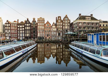 AMSTERDAM NETHERLANDS - 16TH FEBRUARY 2016: Old Buildings along the Damrak in Amsterdam during the day. Boats can be seen.