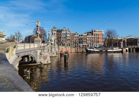 AMSTERDAM NETHERLANDS - 16TH FEBRUARY 2016: A view of the Blauwbrug Bridge in Amsterdam. Buildings can be seen on the over side of the Amstel canal.