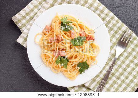 Pasta Carbonara with ham and cheese on checkered towel. Top view.