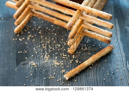 Bunch Of Homemade Grissini Breadsticks In A Glass Jar On Wooden Surface